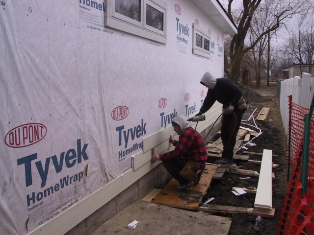 """The first """"sticks"""" of cementuous siding get installed."""