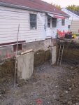 Now that the hole is dug out, the first-poured pillars supporting the existing foundation are quite evident.