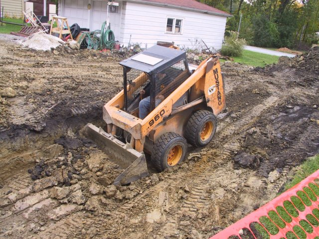 """""""Bobcat"""" gets rear wheels in the air while doing the initial digs for the basement under the addition"""