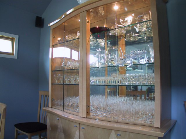 This is a closer view of the dining room hutch with glass shelves, mirrored back, filled with glassware.