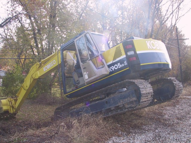 """The back hoe was now """"land locked"""" because of the big hole, so it was taken out on the access road along the RR embankment... I didn't know these could fly!"""