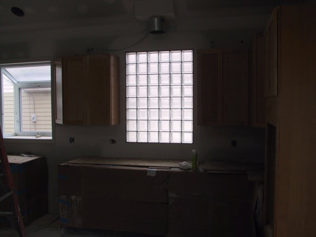 The glass block window that will be the cooktop backsplash (and will backlight the stainless vent hood) is now installed.
