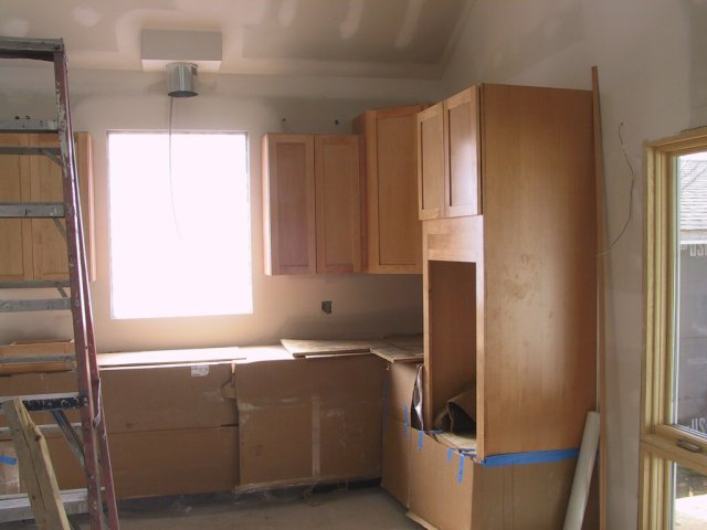 The wall straightened, kitchen cabinets get installed.  This is the oven cabinet on the West wall and cooktop base under the window opening.