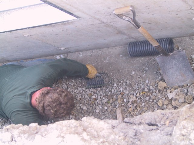 """French"" drains are installed around the perimeter and a drain for each window well is cut into this."