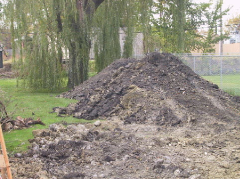 """Initial excavation """"tailings"""" of topsoil piled in the back yard for later backfill"""