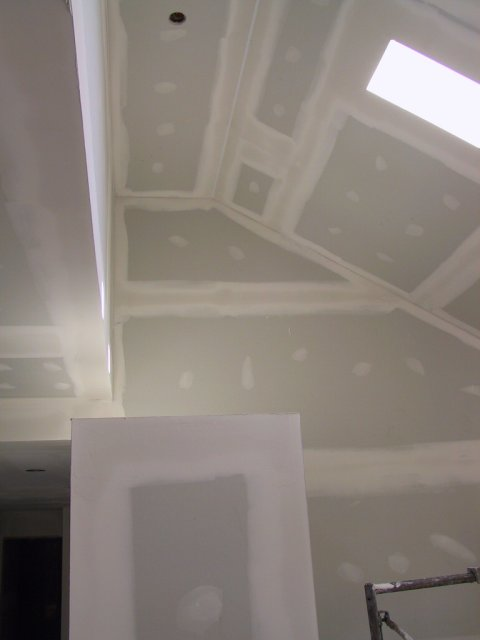 The entrance off the driveway is adjacent to the open basement stairs, illuminated by two skylights. This is the ceilingd detail showing the 9' ceiling and 7' closet of the hallway.