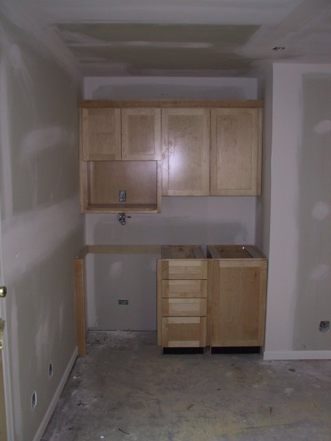 The finish carpenters make short work of getting them installed, ready for granite counters and the refrigerator. Just to the right are the French doors leading to the hall...