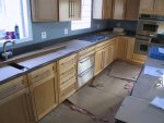 """Once again, the counter tops are covered in cardboard for protection.  The two deep drawers from the cabinet next to the cooktop have been removed and replaced with a pair of 27"""" warming ovens (drawers)."""