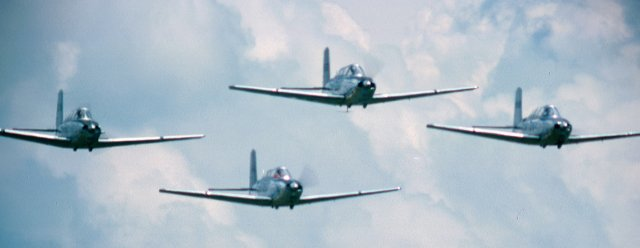 A group of single-engine aircraft in formation at an air show (most likely DuPage (Illinois) County Airport) sometime in the 1980s.Ektachrome (HS), 800mm telephoto lens.